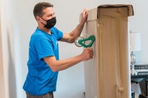 Picture of our movers wearing a mask while taping boxes for a move